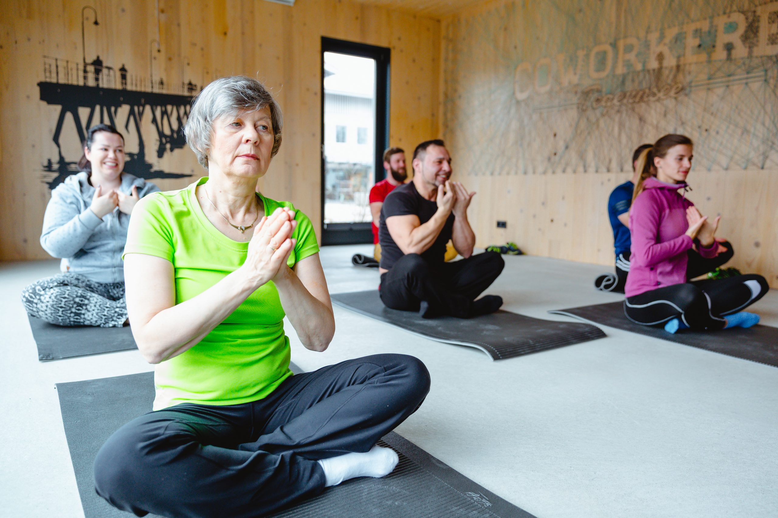 Menschen im Schneidersitz gemeinsam in einem Raum beim Yoga